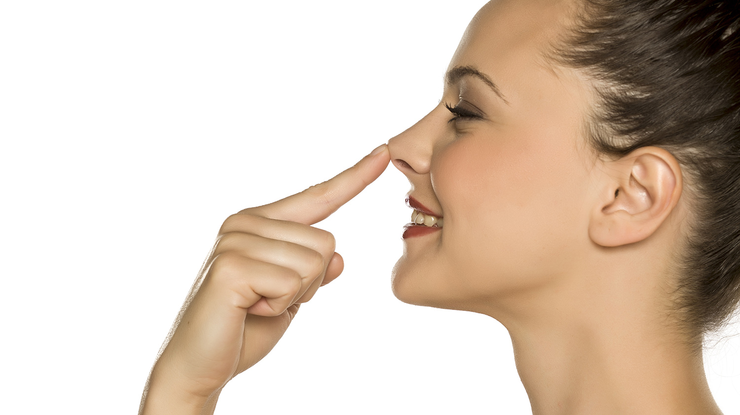 profile of young happy woman touches her nose with her finger on